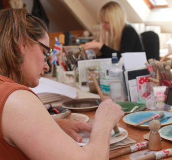 hand decorating pottery using stencils in the workshop