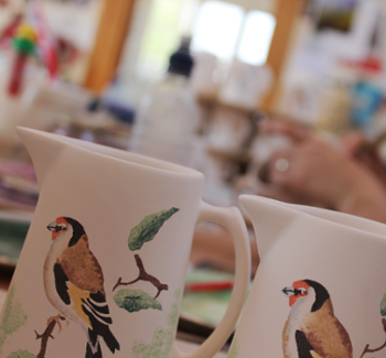 pattern working pottery - a jug with a Goldfinch pattern in the workshop